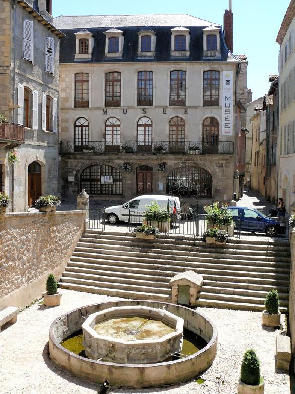 Place de la Fontaine classée monument historique en 1920, fontaine du Griffoul édifiée en 1336 par les Consuls et musée Urbain Cabrol.