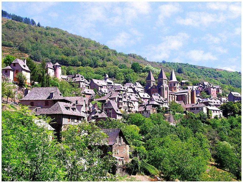 Au fond d'un cirque, le village médiéval de Conques est tassé autour de l'abbatiale Sainte-Foy, à mi-pente sur le versant ensoleillé. Les maisons disposées en espalier tournent leurs façades principales vers le Midi.