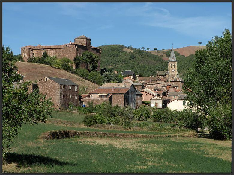 Ce château épiscopal du XIV° siècle  en grès rouge, classé monument historique, domine le bourg fortifié sur un méandre du Dourdou.
