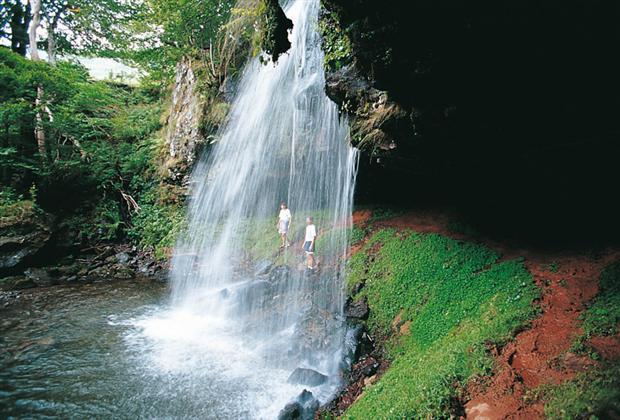 A l'arrière plan, une petite grotte donne une touche colorée à la chute d'eau.