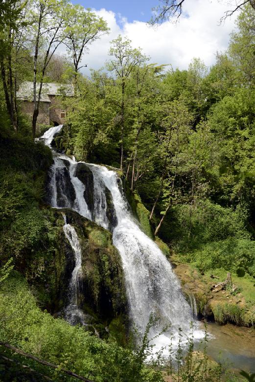 Une petite passerelle menant à une cascade permet d'avoir une vue d'ensemble des bâtiments du Moulin de Terral