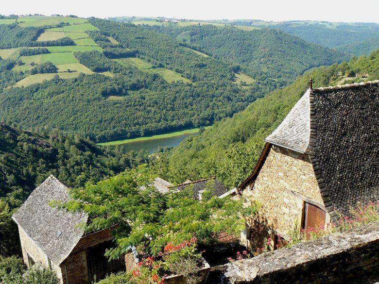 La Vinzelle, perchée sur un éperon rocheux qui surplombe le Lot (côté rive droite), se situe à une quinzaine de kilomètres de Conques (Aveyron) et à la limite du département du Cantal.